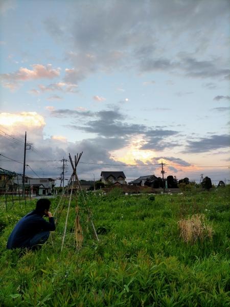 ノラ作業の後に畑を眺める。空には満月のような月が出ている。後ろを向くと、真っ赤な夕陽が武甲山に沈んでいた。